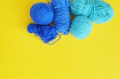 Blue ball of woollen thread. Yellow background. The view from the top. Threads, wool, blue and turquoise colors with a pair of scissors. Material for a hobby Stock Photography