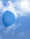Blue balloon in bright sky Stock Image