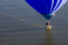 Blue balloon over water. Blue hot air balloon skims water surface, splash and dash Royalty Free Stock Photography