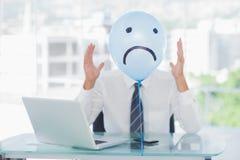 Blue balloon with sad face hiding angry businessmans face Stock Photos