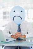 Blue balloon with sad face hiding businessmans face Stock Photos