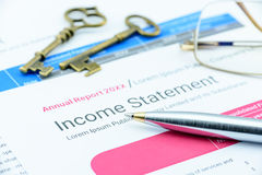 Blue ballpoint pen on a corp's income statement with two antique brass keys and eye glasses. Stock Photos