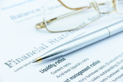 Blue ballpoint pen and eye glasses on a company's financial analysis check list. Stock Photography