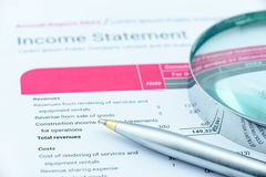 Blue ballpoint pen and a magnifier on an association's income statement. Royalty Free Stock Photography
