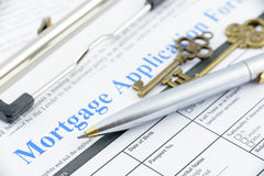 Blue ballpoint pen and two vintage brass keys on a mortgage application form. Stock Images