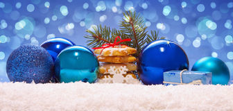 Blue balls and christmas cookies on snow . Stock Photos