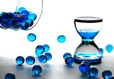Blue balls and clepsydra. Blue balls falling from wineglass and clepsydra Royalty Free Stock Images