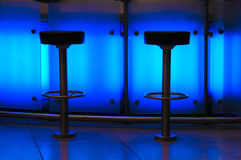 Blue bar. Two bar stools in blue light royalty free stock images