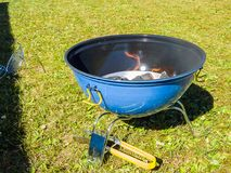 A blue barbeque grill with charcoal burning with flames. A blue and black barbeque grill with charcoal burning with orange flames waiting for the coal to be Royalty Free Stock Images