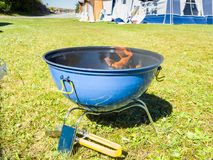 A blue barbeque grill with charcoal burning with flames. A blue and black barbeque grill with charcoal burning with orange flames waiting for the coal to be Royalty Free Stock Photos