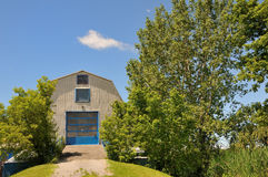 Blue Barn. A raised blue barn with wooden ramp and garage door Royalty Free Stock Photo