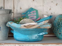 Blue basket with beach decoration. In foreground sinking bucket middle blue basket with starfish old wood right ceramic vase background weathered old white wood Stock Images