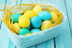 Blue basket of colored eggs Royalty Free Stock Images