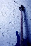 Blue bass guitar. Stands near the wall stock photo