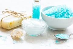 Blue bath salt, body cream and shells for spa on white table bac. Natural blue bath salt, body cream and shells for spa on white table background Stock Photos