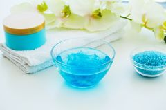 Blue Bath Salt, Body Cream and Shells For Spa on White Table Bac. Kground Royalty Free Stock Photos