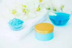 Blue Bath Salt, Body Cream and Shells For Spa on White Table Bac. Kground Stock Image
