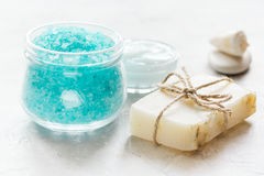 Blue bath salt, body cream and shells for spa on white table background Stock Images