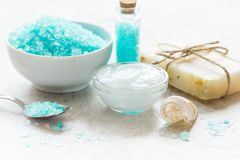 Blue bath salt, body cream and shells for spa on white table background Royalty Free Stock Images