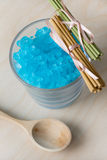 Blue Bath Salt in Glass. Aromatic sticks and wood spoon Royalty Free Stock Image