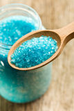 Blue bath salt in wooden spoon Stock Images