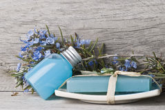 Blue bath salts and gel. A jar with rosemary gel and bath salts in blue and some rosemary branches with flowers Stock Photos