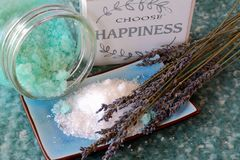 Blue bath salts and lavender flowers. Blue peppermint and eucalyptus bath salts on a soft background with dried lavender flowers and a Choose Happiness sign Stock Photo