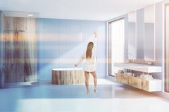 Blue bathroom tub, shower and sink, woman. Woman in modern bathroom with blue walls, white floor, wooden bathtub, shower with wooden and glass walls and double stock photo