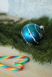 Blue bauble on christmas tree and candy canes Royalty Free Stock Image