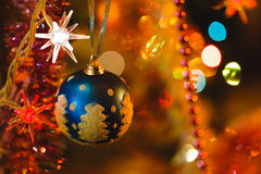 Blue bauble in Christmas tree surrounded by colourful lights Stock Photography