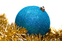 Blue bauble on gold tinsel Stock Photo