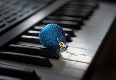 A blue bauble is lying among the synthesizer keys royalty free stock photo