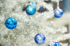 Blue baubles on silver artificial christmas tree Stock Photos