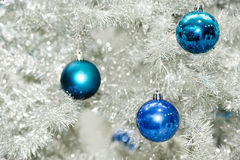 Blue baubles on silver artificial christmas tree Royalty Free Stock Photography