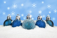 Blue baubles in the snow Royalty Free Stock Image