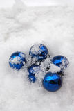 Blue baubles in snow Royalty Free Stock Photos
