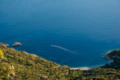 Blue bay and boat  under Lubenice town in Cres Royalty Free Stock Photography
