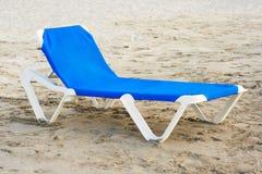 Blue beach chair in a deserted beach. Blue plastic beach chair in a deserted beach Stock Image