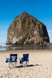 Blue beach chairs put in front of the huge Haystack rock in Cannon Beach, Oregon, USA. royalty free stock images