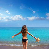 Blue beach girl with bikini holding starfish rear view Stock Photography