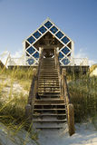 Blue beach house. Blue and white beach front property with stairs leading down to sandy white beach Stock Image