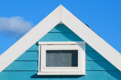 Blue beach hut has room with a view of the beach. Blue beach hut gable with window against blue summer sky stock photos