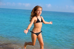 Blue beach kid girl with bikini jumping and running Royalty Free Stock Photo