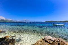 Blue beach at Korcula Croatia with boat and swimmers Royalty Free Stock Photos