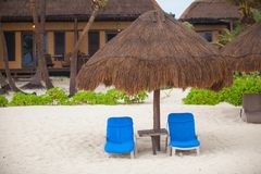 Blue beach loungers under thatched umbrellas on a Stock Photo