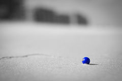 Blue Beach Marble. A lone blue marble sits on a white sand beach Royalty Free Stock Images