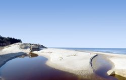 Blue beach panorama. Stream of water in front of some concrete blocks on a  lonely beach, empty horizon, Baltic sea. Abandoned structures, military bunkers. Wide Royalty Free Stock Photography