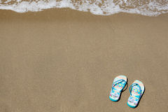 Blue beach slippers on sandy beach with copy space Royalty Free Stock Images