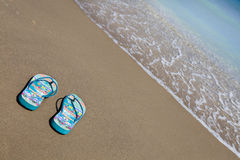 Blue beach slippers on sandy beach with copy space Royalty Free Stock Photography