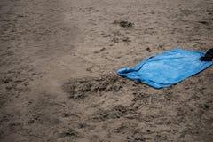 Blue beach towel on sand, sea as background stock photos